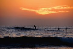 Orange sunset over the Pacific with paddle-boarders Royalty Free Stock Photos