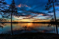 Orange sunset over the pine trees and lake  during the white nig. Hts in Karelia Royalty Free Stock Image