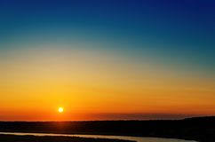 Orange sunset over river and blue sky Stock Images