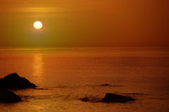 Orange sunset over the sea with rocks Stock Images