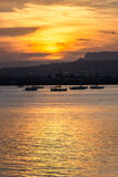 Orange sunset over the sea of Syracuse, Ortigia, Sicily, Italy. With moored boats and mountains on the horizon. Vertical shot Stock Photos