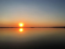 Orange sunset over water surface. twilight on the lake. Royalty Free Stock Photography
