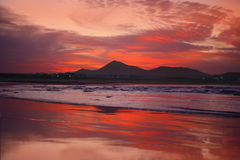 Orange sunset in playa Famara, Lanzarote Stock Photos