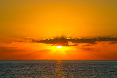 Orange sunset with rays shines through the clouds at Paphos coas Stock Images