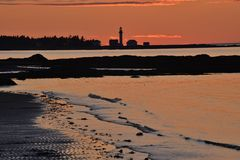 Orange sunset reflected in bay and beach of rising tide Stock Image