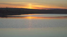 Orange sunset reflected on surface of lake on a summer day. Sun goes feather clouds. On loch there is a small ripple. Sundown is time when horizon appears or stock footage