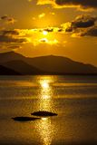 Orange sunset at the sea with mountains Stock Photos