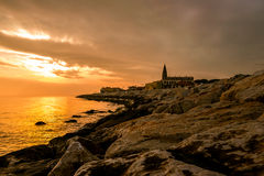 Sunset on rock pier with church and calm sea stock photo