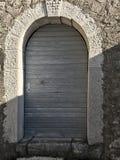 Old rustic wooden door in the village. Grey wooden rustic door for conserve wines Royalty Free Stock Images