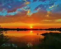 Orange sunset sky reflected on water Royalty Free Stock Photo