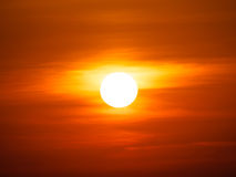 Orange Sunset. Sun shining bright during abstract bright orange sunset and clouds on the sky stock images