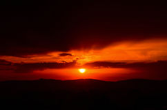 Orange Sunset. With sun and soft light rays visible through dark cloud cover Royalty Free Stock Photography