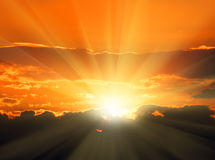 Orange sunset with sunbeams. Beautiful orange sunset with sunbeams and dark clouds Royalty Free Stock Images