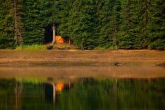 Orange sunset with tent on lake Stock Image
