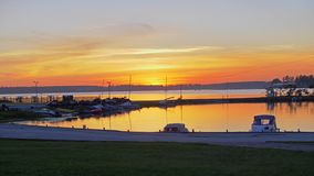 Orange sunset in the yacht club. Boats are parked on the water. stock video
