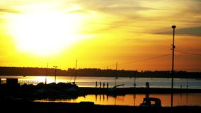 Orange sunset in the yacht club. Boats are parked on the water. stock video footage