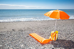 Orange sunshade at a black beach Stock Photos