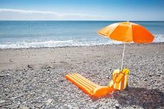 Orange sunshade at a black beach Stock Photos