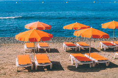Orange sunshades and deckchairs against ocean royalty free stock photography