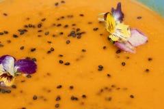 Orange Suppe mit schwarzen Samen des indischen Sesams und frischem Stiefmütterchen blüht - gesunden kochenden Konzepthintergrund  Stockfotos