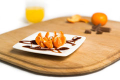 Orange Suprise. Picture of one pealed and one unpeeled orange with chocolate sauce on Stock Image