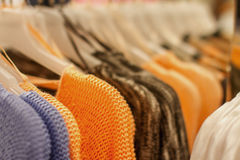 Orange sweater on a hanger in the store Stock Image
