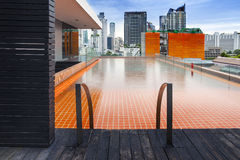 Orange swimming pool on rooftop with modern buildi Royalty Free Stock Photography