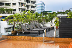 Orange swimming pool on rooftop with modern building. Stock Photography