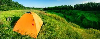 Orange tält på en grön kulle ovanför en ravin royaltyfria bilder