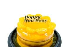 Orange tårta med isolerad guld- lycklig text för nytt år Royaltyfri Foto