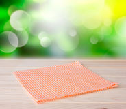 Orange table cloth plaid on wooden table with natural background. Tablecloth textile napkin on wooden table closeup with green natural bokeh background.Kitchen Royalty Free Stock Photography