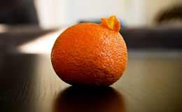 Orange. On table partly peeled Stock Image