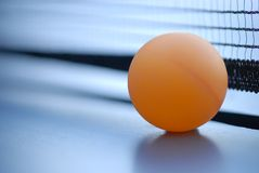 Orange table tennis ball on blue table with net. Selective focus Royalty Free Stock Images