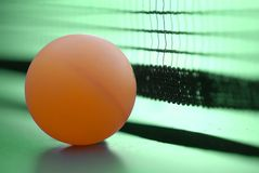 Orange table tennis ball on green table with net. Selective focus Royalty Free Stock Photography