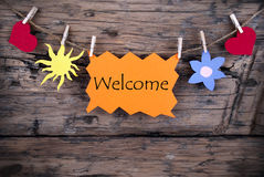 Orange Tag with Welcome. An Orange Tag Hanging on a Line with Different Symbols witht the Word Welcome on it Royalty Free Stock Images