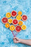 Orange, tangerine and grapefruit in conjunction as balloons, hand holding the strings. Royalty Free Stock Photos