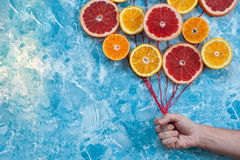 Orange, tangerine and grapefruit in conjunction as balloons, hand holding the strings. Royalty Free Stock Photography