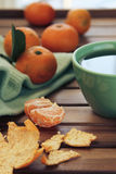 Orange tangerine and mandarin slices, green  cup of tea Royalty Free Stock Photos