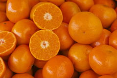 Tangerines or clementines in a pile with one halved. Crate of juicy tangerines on an open air fruit market stall , easy peel fruit like clementine. These small Royalty Free Stock Photography