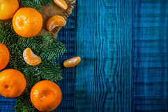 Orange tangerines with fir branches. Christmas composition on the blue wooden background.Top view Royalty Free Stock Photos
