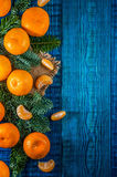 Orange tangerines with fir branches. Christmas composition on the blue wooden background.Top view Royalty Free Stock Photo
