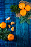 Orange tangerines with fir branches. Christmas composition on the blue wooden background.Top view Stock Image