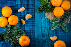 Orange tangerines with fir branches. Christmas composition on the blue wooden background.Top view Royalty Free Stock Images