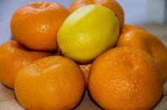 Orange tangerines and yellow lemon on a wooden table stock photos