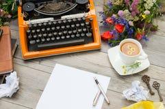 Orange tappningskrivmaskin med koppen av örtte och gamla tangenter Arkivbild