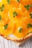 Orange tart with cream and mint macro. vertical top view Stock Photos