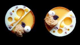Orange tarts with meringues and white chocolate on black background stock photography