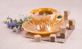 Orange Tasse Tee mit den Stücken des Zuckerrohrs stehend auf jedem oth Stockfoto