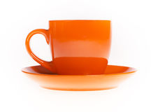 The orange tea mug with saucer Royalty Free Stock Photo