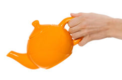 Orange teapot isolated in hand on white background Royalty Free Stock Photo